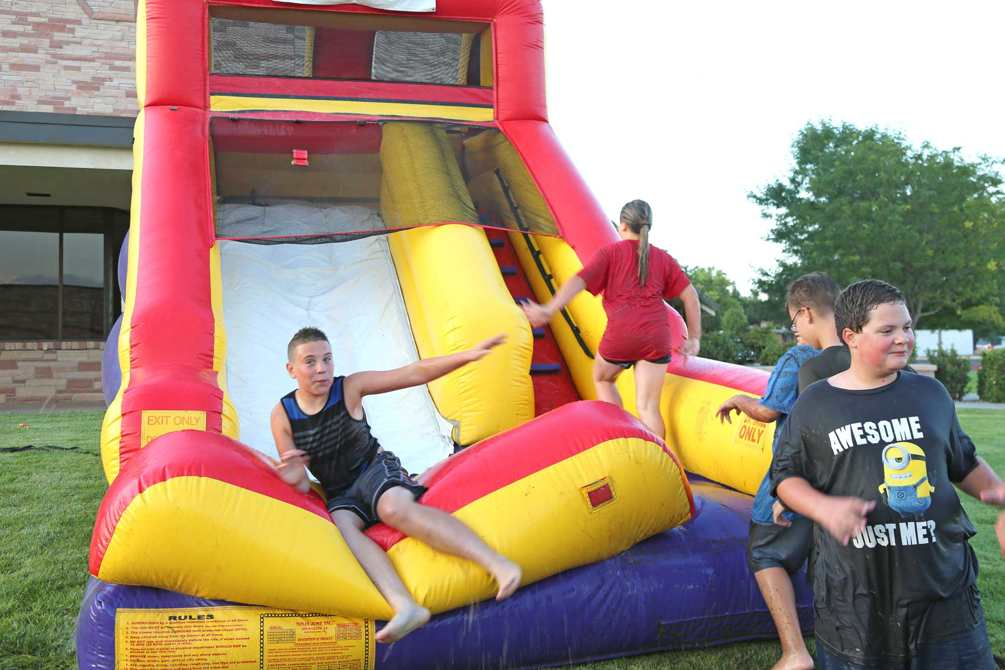 Image 1 of residents using an inflatable water slide