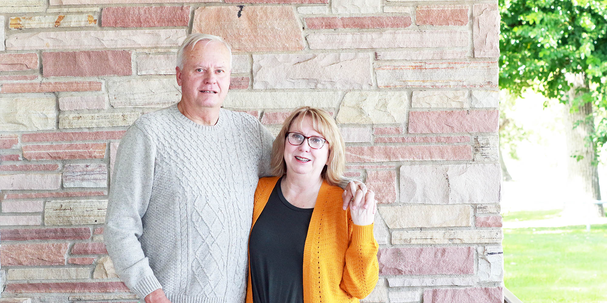 Jesse and Sandy Pape hold hands as they pose in front of a Colorado sandstone building.