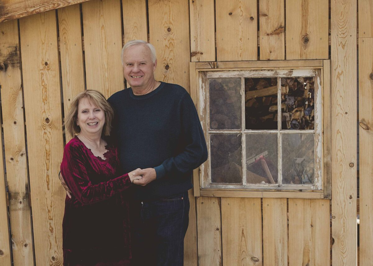 A man and a woman hold hands and smile in front of a cabin.