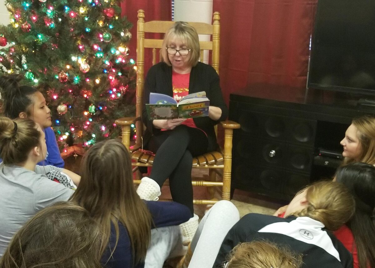 Houseparent Sandy Pape sits in a rocking chair, holding a book. She is beside a Christmas tree. Girls sit at her feet in a circle.