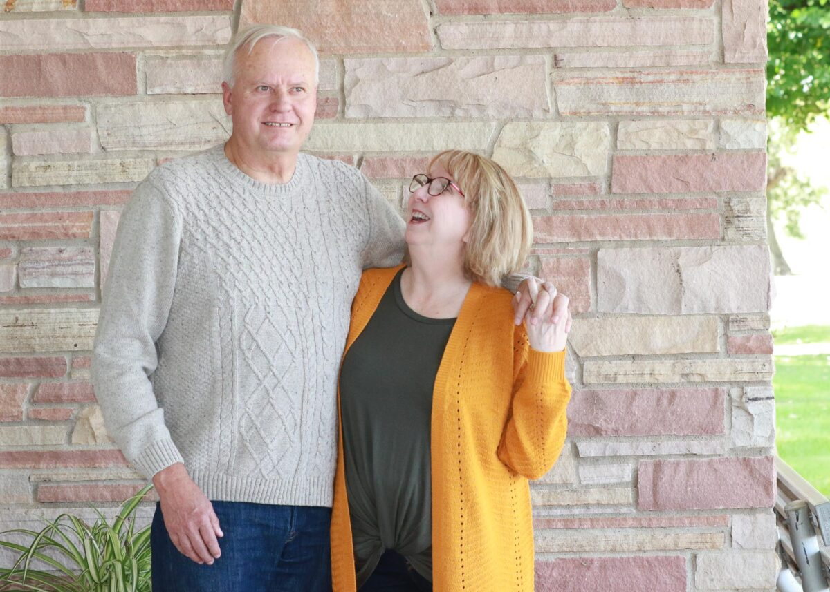 Sandy and Jesse Pape hold hands and laugh toward the camera.